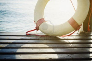 Safety Element - Life Preserver on wood floor, sea as background Stock Photo - 13459845